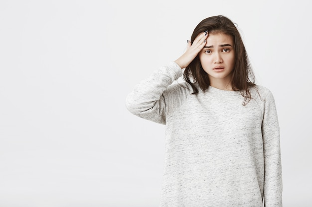 Ritratto di modello femminile europeo stanco e infelice con le sopracciglia aggrottate le sopracciglia e la bocca aperta, tenendo la mano sulla fronte