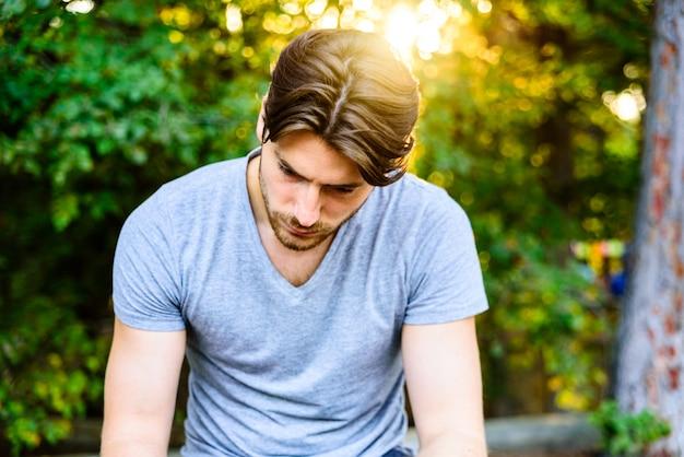 Ritratto di modello guardando in basso con bei capelli, concetto di tristezza negli uomini, grana del film aggiunto e sfondo sfocato.
