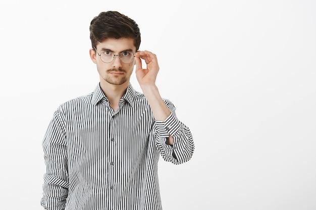 Ritratto di modello maschio nerd dall'aspetto serio con barba e baffi, che tiene il bordo degli occhiali, guardando concentrato, ascoltando attentamente il capo durante la riunione, pronto per iniziare a lavorare sul progetto
