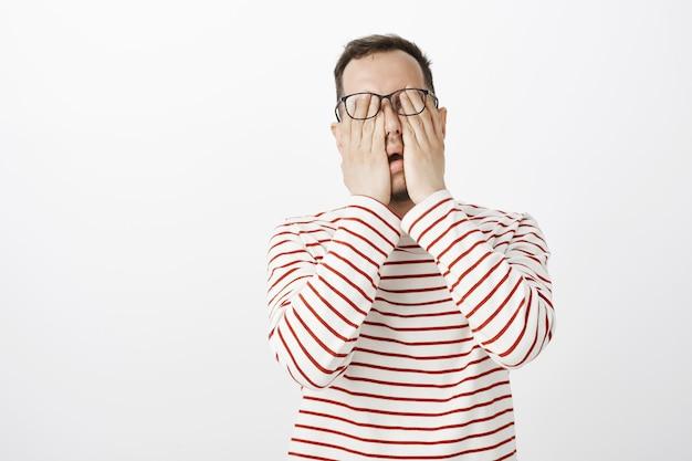 Ritratto di modello maschio scomodo esausto in pullover a righe e occhiali, sfregamento degli occhi, sensazione di dolore o stanchezza dopo aver seduto vicino al computer tutto il giorno
