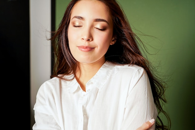 Ritratto di modo di bellezza della giovane donna asiatica sorridente sensuale con capelli lunghi scuri in camicia bianca su verde
