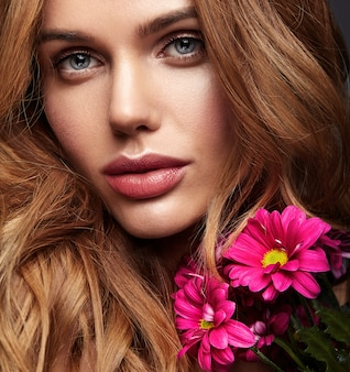 Ritratto di modo di bellezza di giovane modello biondo della donna con trucco naturale e pelle perfetta con la posa luminosa del fiore del crisantemo del? smson