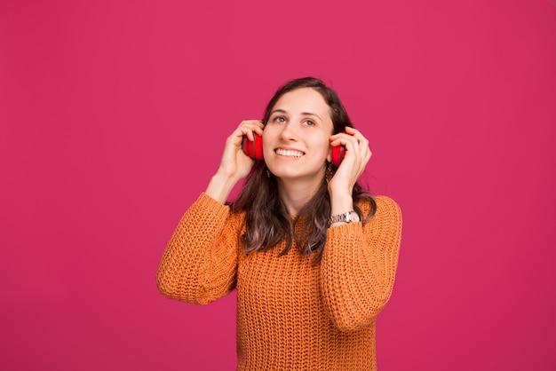 Ritratto di musica d'ascolto della giovane donna alle cuffie senza fili