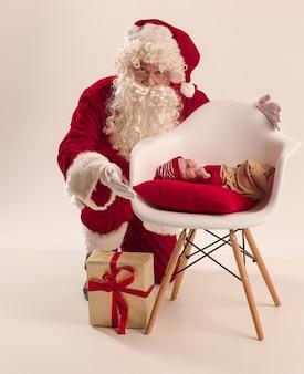 Ritratto di natale della piccola neonata sveglia, vestita in abiti natalizi e uomo che indossa il costume e il cappello di babbo natale, girato in studio, orario invernale. il natale, concetto di vacanze