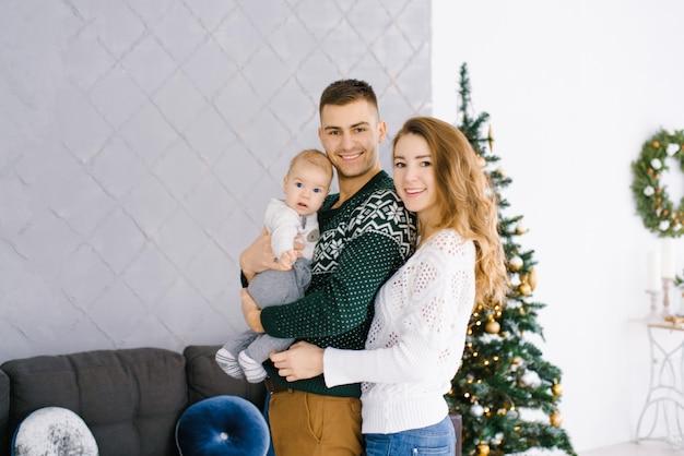 Ritratto di natale di una famiglia con un giovane figlio