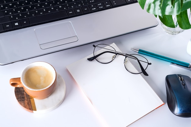 Ritratto di natura morta di computer, tazza di caffè sul tavolo e notebook in ambiente luminoso.