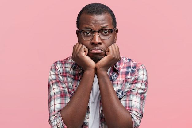 Ritratto di orinato sorrorful maschio dalla pelle scura curve il labbro inferiore e tiene le mani sotto il mento, vestito con una camicia casual e occhiali