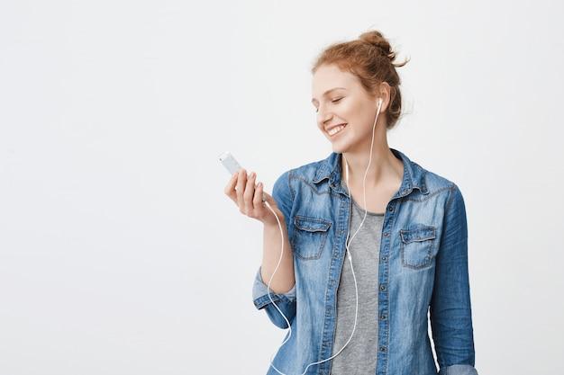 Ritratto di ottimista positivo giovane ragazza allo zenzero guardando lo schermo dello smartphone durante l'ascolto di musica o la visione di video in cuffia