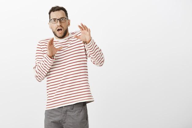 Ritratto di padre europeo adulto terrorizzato scioccato in occhiali e pullover a righe, piegandosi all'indietro con le mani alzate