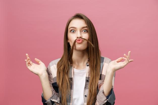 Ritratto di pazza adorabile giovane donna che gioca con i suoi capelli