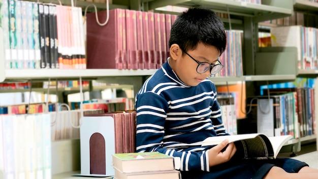 Ritratto di piccola lettura asiatica del ragazzo sul pavimento delle biblioteche alla scuola elementare.