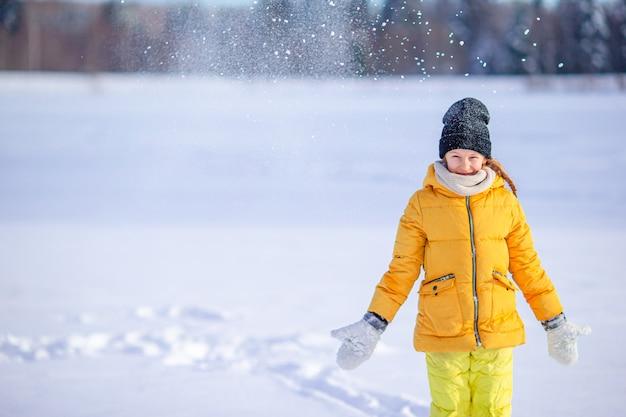 Ritratto di piccola ragazza adorabile nel giorno di inverno soleggiato della neve