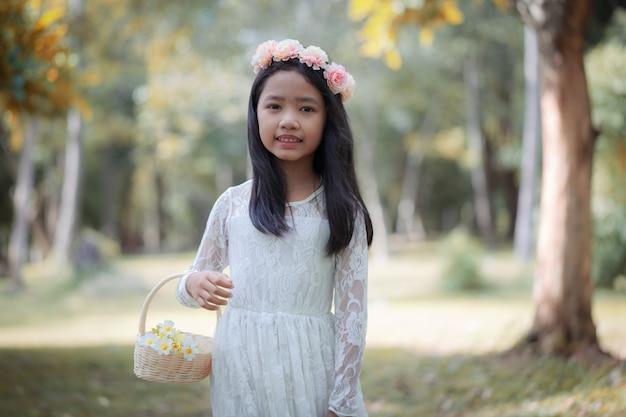 Ritratto di piccola ragazza asiatica che sorride nella foresta della natura
