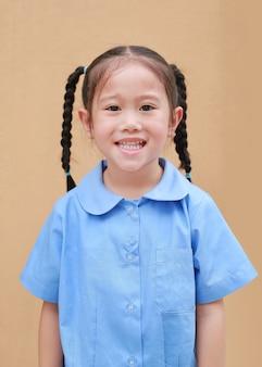 Ritratto di piccola ragazza asiatica in uniforme scolastica.