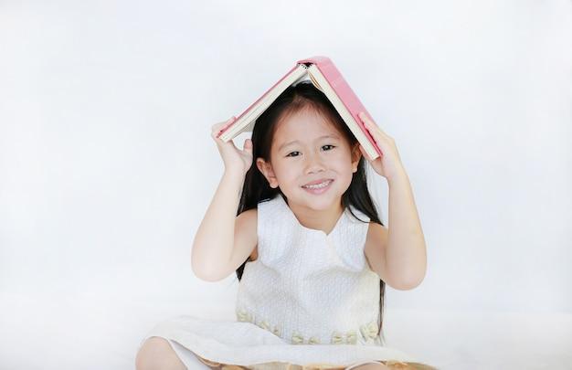 Ritratto di piccola ragazza asiatica posto libro con copertina rigida sulla sua testa e guardando la telecamera su sfondo bianco.