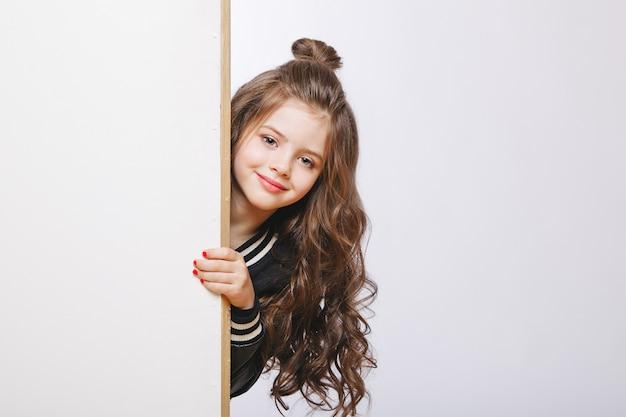 Ritratto di piccola ragazza hipster guardando fuori. acconciatura riccia copia-spazio