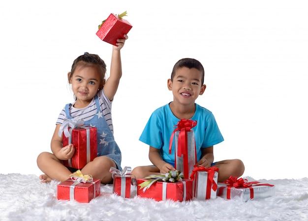 Ritratto di piccoli ragazzo e ragazza asiatici felici con molti contenitori di regalo isolati su bianco