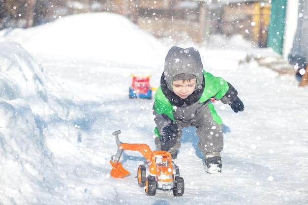 Ritratto di piccolo bambino sveglio che si siede sulla neve e che gioca con il suo giocattolo giallo del trattore nel parco. bambino che gioca all'aperto. ragazzo felice con il giocattolo di costruzione. concetto di stile di vita