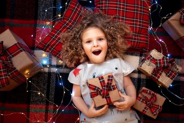 Ritratto di piccolo bambino sveglio sorridente in pigiami di natale di festa che tengono il contenitore di regalo. vista dall'alto.