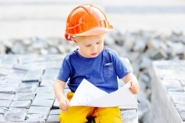 Ritratto di piccolo costruttore sveglio in elmetti protettivi che legge costruzione che disegna all'aperto. l