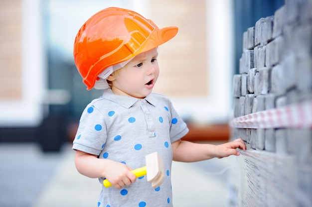 Ritratto di piccolo costruttore sveglio in elmetti protettivi con il martello che lavora all'aperto