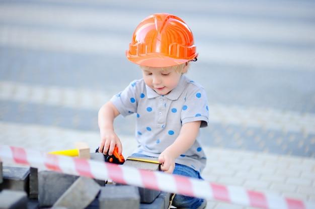Ritratto di piccolo costruttore sveglio in elmetti protettivi con il righello che lavora all'aperto