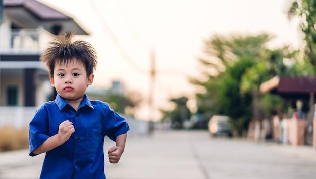 Ritratto di piccolo ragazzo asiatico sveglio che si rilassa giocando e divertendosi in esecuzione nel parco cittadino