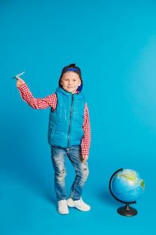 Ritratto di piccolo ragazzo di scuola divertente con l'aeroplano di carta del giocattolo