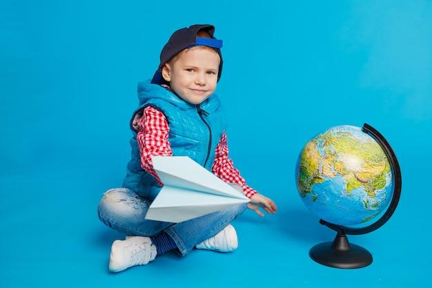 Ritratto di piccolo ragazzo divertente con cappuccio e giocattolo aereo di carta