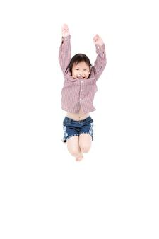 Ritratto di piccolo salto asiatico felice del bambino isolato su bianco