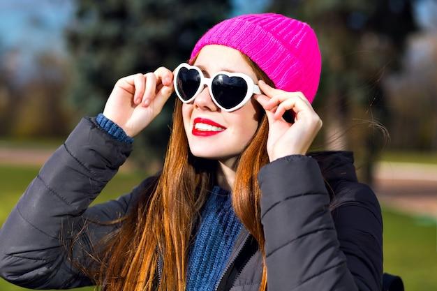 Ritratto di primavera soleggiata di donna zenzero sorridente allegra felice in posa al parco, godersi una giornata di sole, cappello hipster punk luminoso, occhiali da sole dal cuore, labbra rosse, parka caldo, umore positivo.