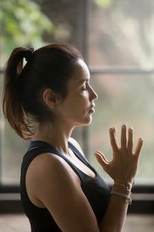 Ritratto di profilo di giovane donna attraente con namaste