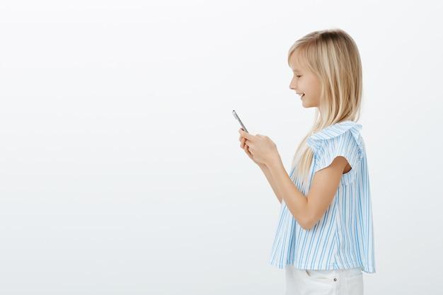 Ritratto di profilo di ragazza bionda gioiosa positiva in camicetta blu alla moda, che tiene smartphone e sorride allo schermo