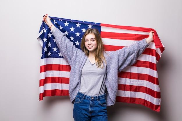 Ritratto di ragazza abbastanza teenager che tiene bandiera usa isolata su grey. celebrazione del 4 luglio.