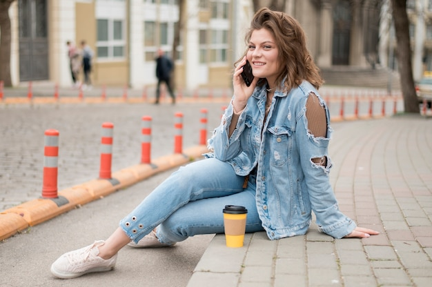 Ritratto di ragazza alla moda parlando al telefono