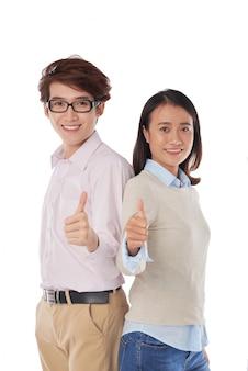 Ritratto di ragazza asiatica e ragazzo in piedi schiena contro schiena pollici in su