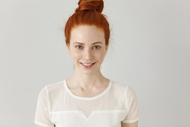 Ritratto di ragazza attraente rossa con le lentiggini che guarda l'obbiettivo e sorride felicemente