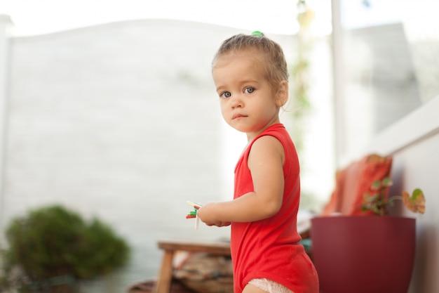 Ritratto di ragazza bionda con gli occhi azzurri nel parco. bambino, sorriso alto vicino della neonata