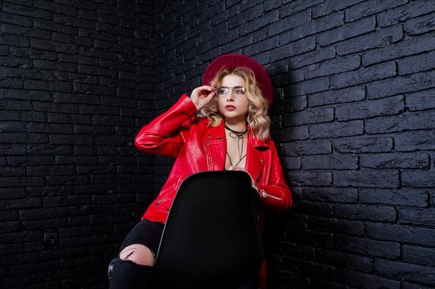 Ritratto di ragazza bionda in cappello rosso, occhiali e giacca di pelle poste sulla sedia contro il muro di mattoni.