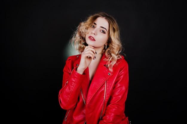 Ritratto di ragazza bionda in giacca di pelle rossa contro.