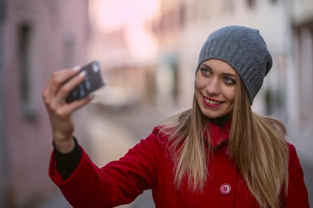 Ritratto di ragazza bionda, prendendo selfie foto con lo smartphone.