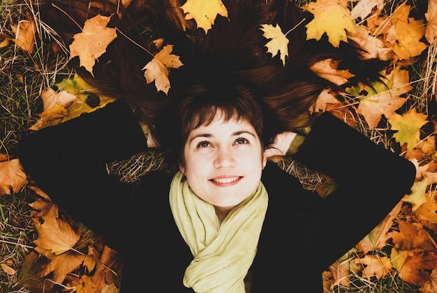Ritratto di ragazza bruna nel parco d'autunno.
