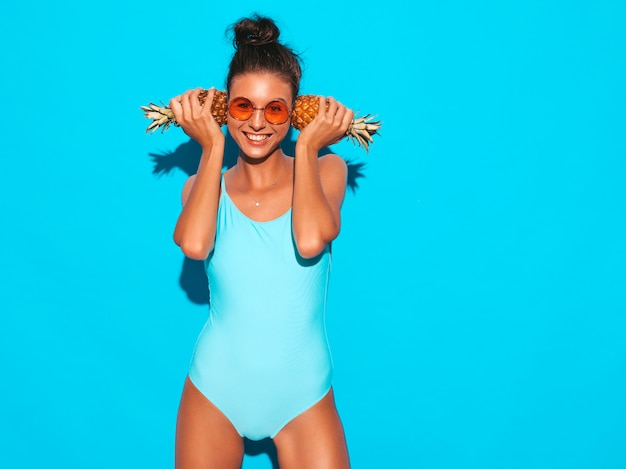 Ritratto di ragazza bruna sorridente in costume da bagno estivo e occhiali da sole. donna sexy con piccoli ananas freschi. modello positivo che posa vicino alla parete blu. lo ha tenuto vicino alle orecchie