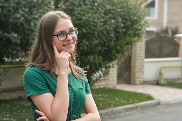 Ritratto di ragazza carina con gli occhiali, sorridente
