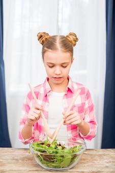 Ritratto di ragazza carina mescolando l'insalata di verdure a foglia con cucchiaio di legno