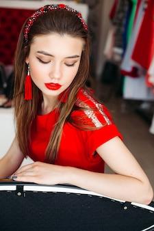 Ritratto di ragazza che indossa una fascia per capelli rossa e lucida