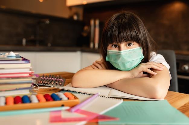 Ritratto di ragazza con maschera protettiva sul viso a casa. concetto di apprendimento online