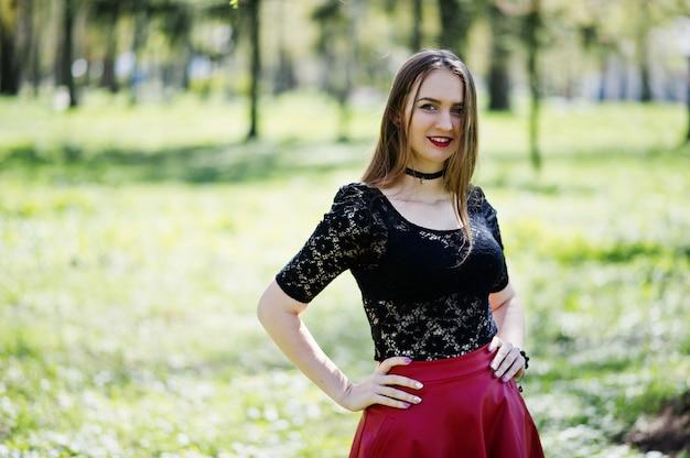 Ritratto di ragazza con trucco luminoso con labbra rosse, collana girocollo nera sul collo e gonna di pelle rossa al parco di primavera.
