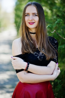 Ritratto di ragazza con trucco luminoso con labbra rosse, collana girocollo nera sul collo e gonna di pelle rossa.