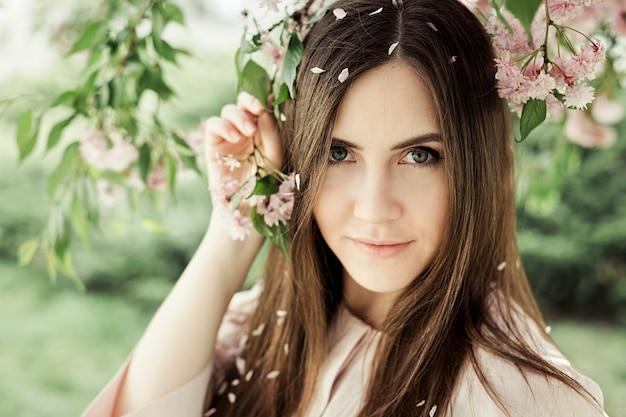 Ritratto di ragazza con un ramo di sakura